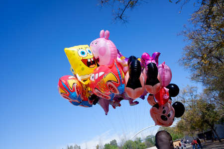 Valencia, Spain - April 15, 2021: Several helium balloons with motifs of children's characters sold by an immigrant.