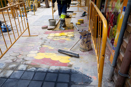 Valencia, Spain - April 15, 2021: Worker repairs the pavement of a pedestrian sidewalk in the city.