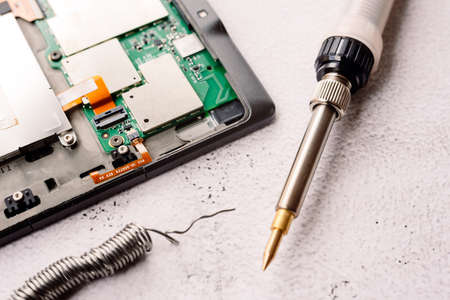 Home repair of an electronic device with a homemade tin soldering iron.