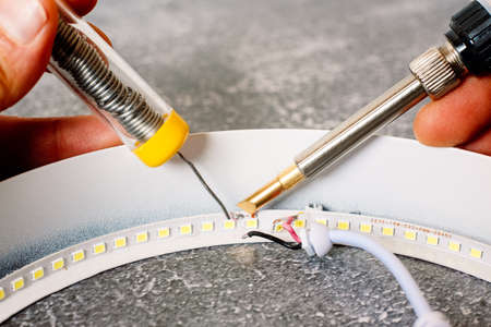 Detail of a tin soldering iron repairing a damaged led strip of lights.