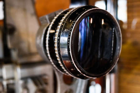 Old anamorphic glass lens on an old movie projector. 免版税图像