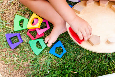 Small hands of a baby trying to fit colored pieces into a game of skill on his lawn. 免版税图像