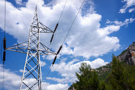 Power lines run through mountains to supply electricity to cities. 免版税图像