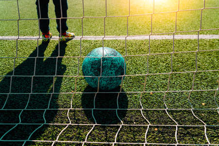 Soccer ball entering a goal defended by a goalkeeper, copy space