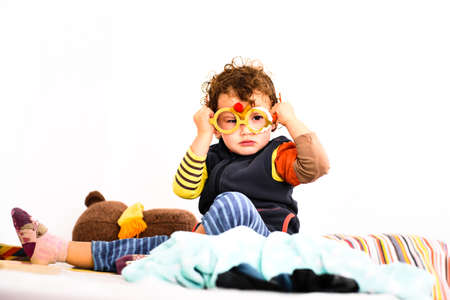 Little baby girl playing with fake glasses alone in her room, isolated on white background.