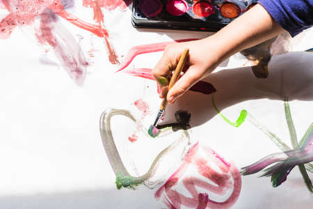 A girl paints watercolors with her stained hand and everything is a mess.
