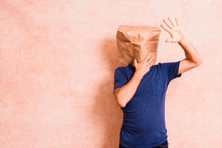Man with paper bag on his head satisfied with his personal achievement, isolated.