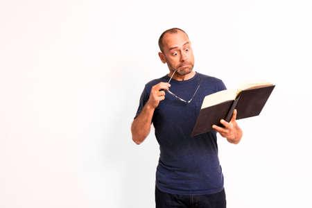 Bald adult man reviews a large study book.