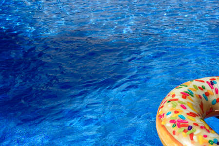 Detail with copy space of a round float in a pool with clean and refreshing waters, background with negative space for summer.