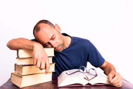 Mature man burdened by how much he must read to learn the world of lawyers and law. 免版税图像