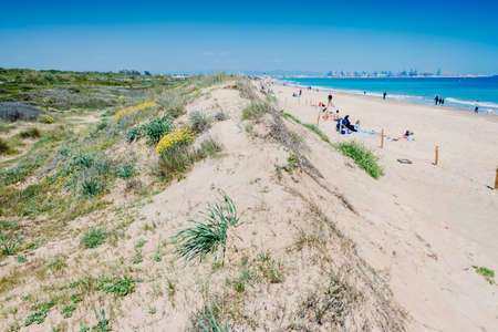 Valencia, Spain - April 21, 2021: Vacationers on a beach, next to the dunes of a protected natural area in El Saler.