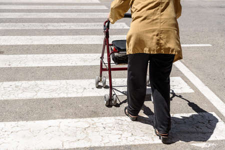Rollator pushed by an elderly woman with mobility difficulties, unrecognizable with copy space.