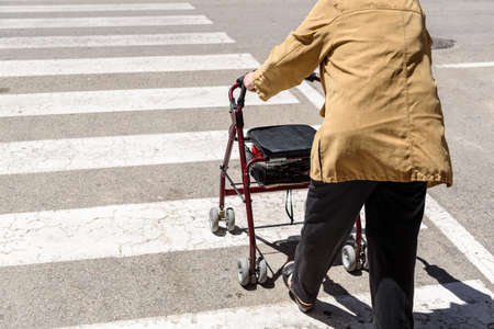 An old woman crosses a pedestrian crossing with the help of a rollator walker.