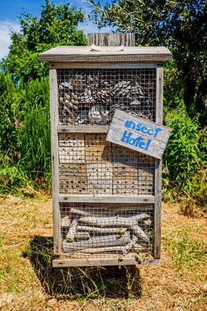 Insect hotel built with old timbers and logs in a garden.