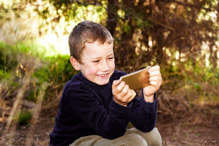 A nice boy in a forest is amazed when he sees a funny video on his mobile phone.
