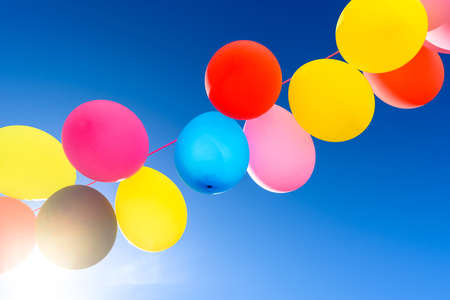 Pretty sunlit solid color balloons viewed from below with blue sky background