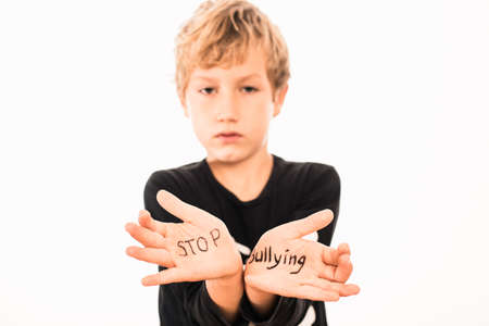 Scared boy shows his hands with the slogan Stop Bullying, isolated on white.