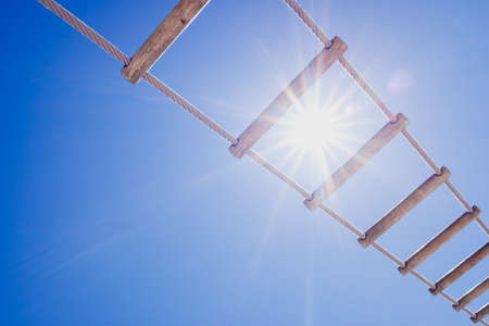 Wooden ladder of an old ship against the midday sun and blue sky background.