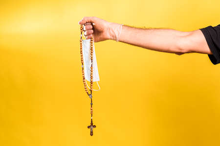 Doctor's hand holds a sanitary mask next to a rosary with a Christian cross. 免版税图像