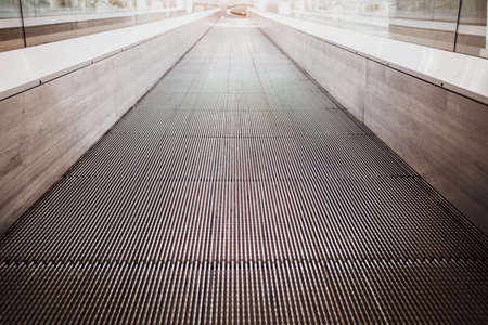 Flat escalator in a shopping mall without people, luminous unfocused background. 免版税图像
