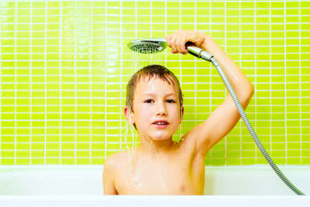 Disgusted expression of a young boy taking a shower and washing himself angrily.