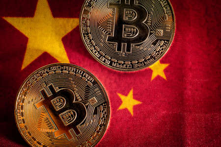 Bitcoin coins on the flag of China, country against its use, recently banned. 免版税图像