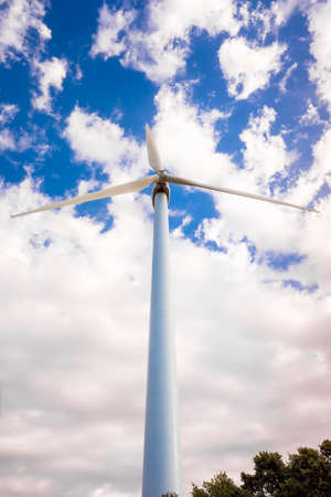 Tall, modern wind turbines spinning to generate renewable electricity with a cloud sky in the background.