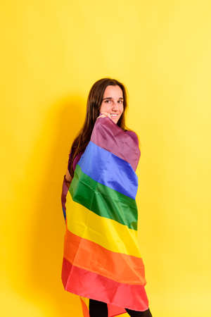 Young woman rolled up in a gay pride flag.