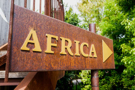 An old signpost with the word Africa made of rusty metal.