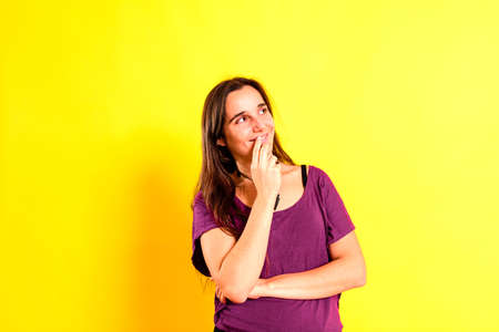 Adorable young woman with thoughtful, pensive gesture dressed casual, isolated on studio background.
