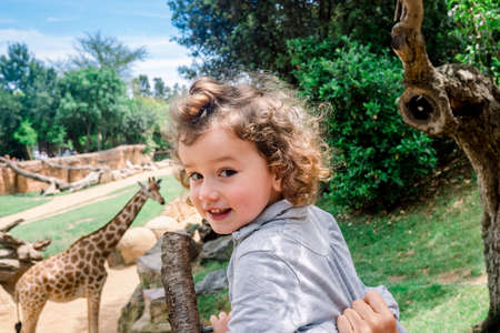 Happy girl on her first visit to a zoo visiting giraffes