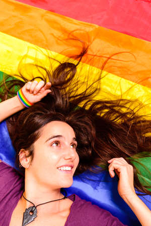 Young student girl lying on a gay flag viewed from above. 免版税图像