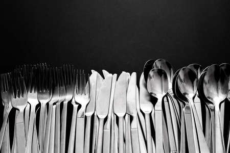 Basic and simple stainless steel cutlery consisting of knives, spoons and forks, isolated on black background with copy space.
