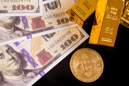 Real bitcoin coin next to gold bars and US dollar bills, concept of the high value of speculative cryptocurrencies. 免版税图像