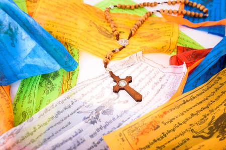 Catholic cross on colorful Tibetan Sanskrit banners with religious prayers 免版税图像