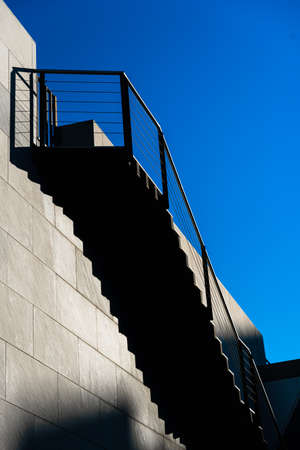 Minimalist wall with shadows from the upper steps of a modern stone staircase.
