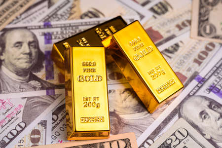 Gold bullion on American dollar bills, concept of commodities to defend against inflation.