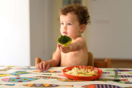 An adorable little girl sitting at the table enjoys eating vegetables directly by hand. 免版税图像