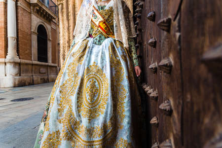 Detail of the traditional fallera dress, with rich golden thread embroidery on a silk skirt.