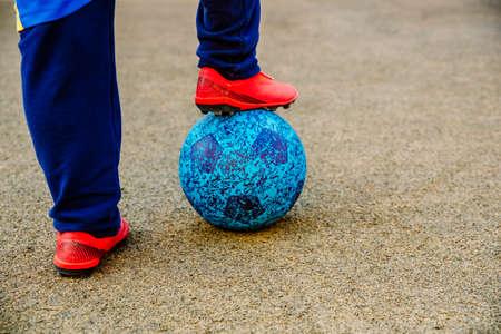 A boy with a soccer ball under his feet.