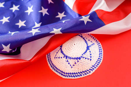Jewish kipa under an American flag, isolated on red background 免版税图像