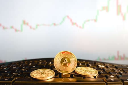 Cardano digital currency, ADA, in gold coins, on a broker's computer keyboard. 免版税图像