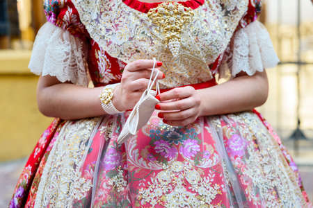 Detail of a Valencian Fallas woman taking off her mask during the Fallas festivities of 2021.