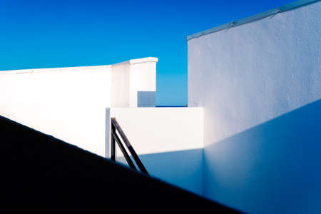 White walls geometric angled shapes of simple and clean design in sunny Mediterranean-style houses.