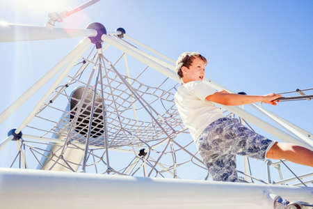 Young boy having fun at an outdoor physical attraction in summer