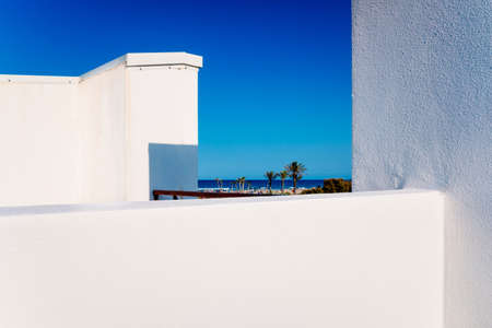 View of the Mediterranean beach from the roof of a simple designed white walled apartment.