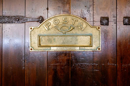 Detail of a wooden door with a letter box with the text Posta, letters in Spanish, in a retro style typical of rural areas.