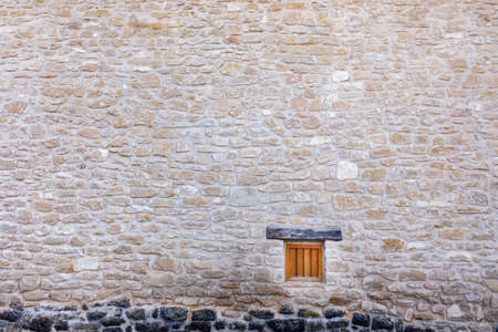 A small, closed wooden window in a large natural stone wall in a rural setting depopulated by immigration.