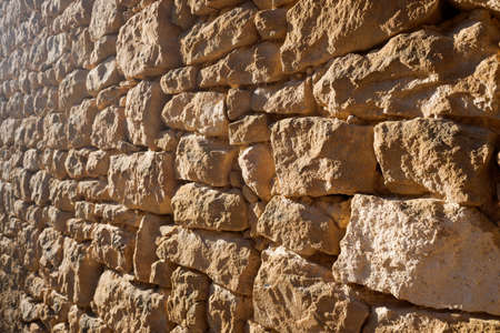 The sun illuminates the natural stone exterior walls of the houses of a small abandoned rural town.