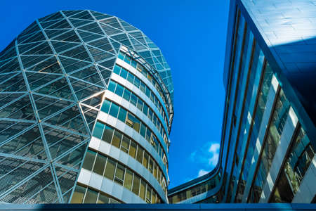Tall office buildings, viewed from below, modern and rounded, with a blue background and copy space. 免版税图像